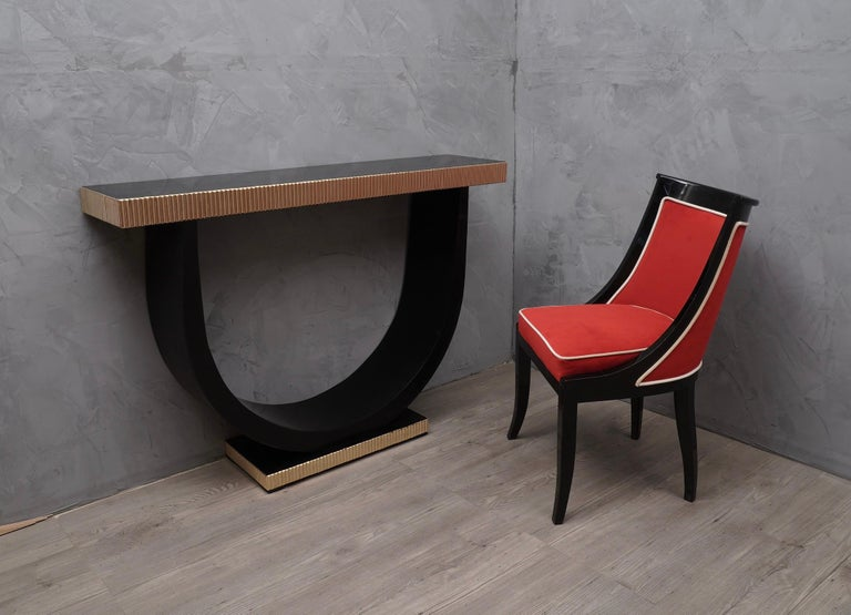 Beautiful console with a very particular design, finely enriched by brass rods and a fantastic polish in black lacquer.  The console, if desired are a couple, is made up of a smooth polished top in black lacquer, with a band made up of small rods in