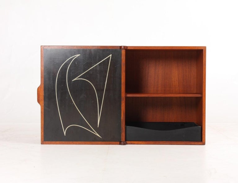 Wall-mounted cabinet in teak. Designed and made in the 1950s. Great original condition.