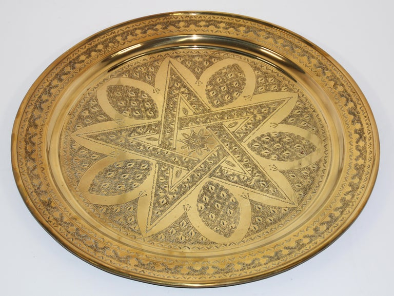 Middle Eastern antique round brass tray. The handcrafted circular brass platter is decorated and hammered with the a star and Moorish designs. Heavy brass with very fine hand chased floral and geometric Arabic designs. Measures: Diameter