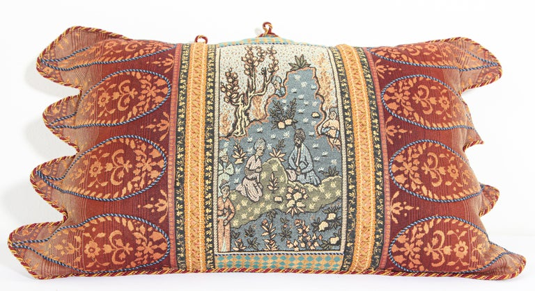 Middle Eastern decorative throw pillow and tapestry. Luxury silk in beige with an accent textile fragment with a Middle Eastern scene and decorative silk trim has been applied to finish the edges.