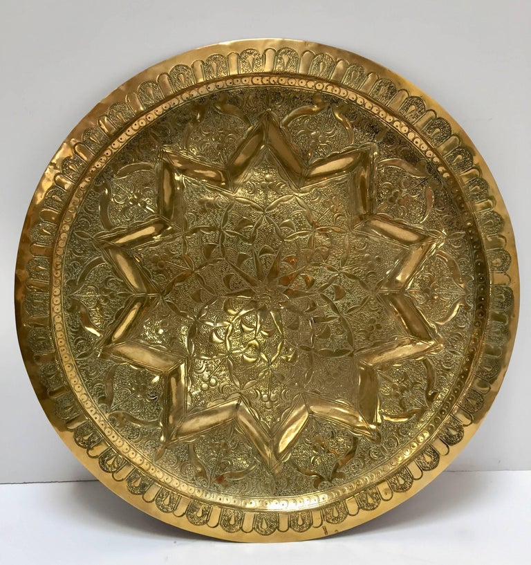 Middle Eastern Persian antique round brass tray. The handcrafted circular brass platter is decorated and hammered with Islamic Moorish designs. Heavy brass with fine floral and geometric designs. Measures: Diameter 19.5