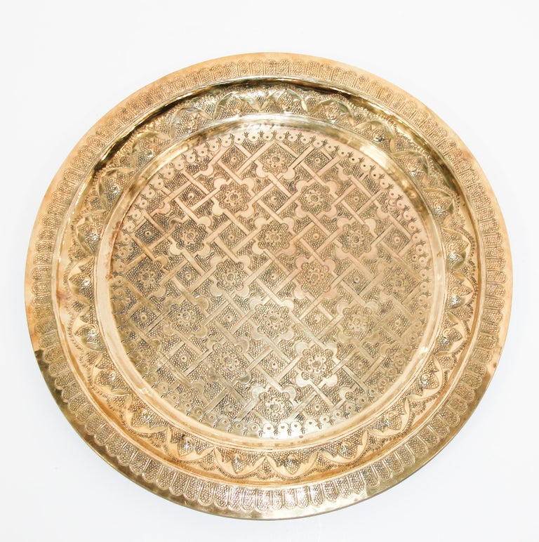 Middle Eastern Syrian antique round brass tray. The handcrafted circular brass platter is decorated and hammered with Islamic Moorish designs. Heavy metal brass with very fine hand chased floral and geometric Arabic designs. 3 different level