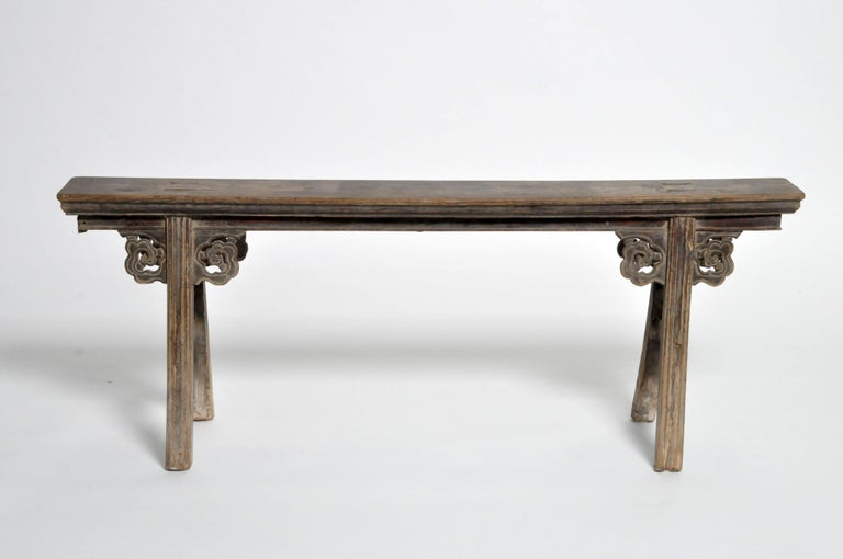 This classic two-person Chinese bench features stretchers, mortise and tenon joinery, and traces of original lacquer. It has a beautiful aged, all-original patina.