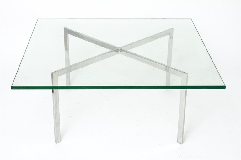 Modernist Barcelona coffee or cocktail table designed originally by Ludwig Mies van der Rohe in 1929 and re-edited by Knoll in the mid-20th century. The table features an X-shaped base with a polished chrome finish and a thick square glass top.