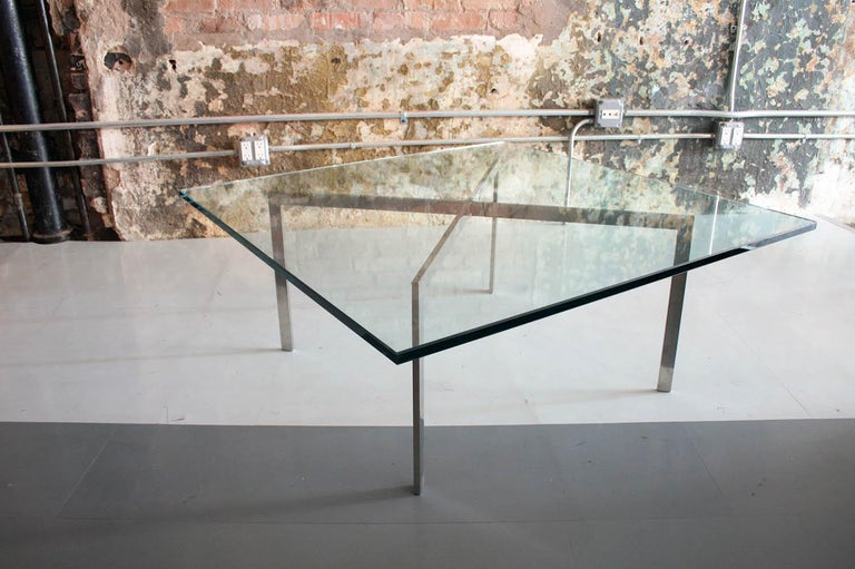This is a Mies van de Rohe for Knoll Barcelona table. The glass is quite thick and the piece features a solid steel base.