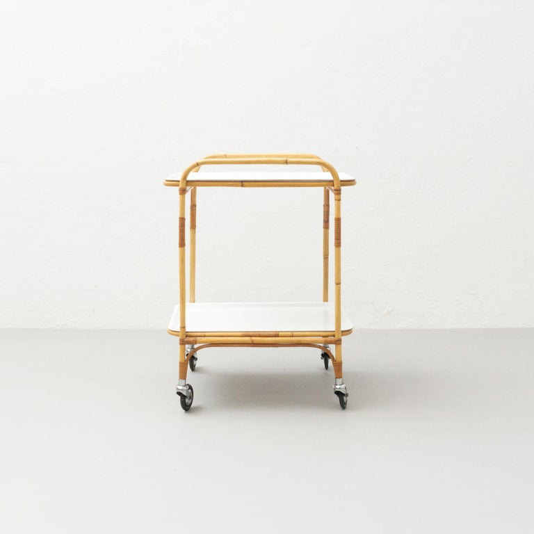 Trolley designed by MMiguel Milà, circa 1960.  In original condition, with minor wear consistent with age and use, preserving a beautiful patina.  Materials: Bamboo Plastic  Dimensions: D: 56 cm W: 46 cm H:74 cm  About the