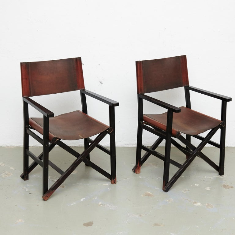 Set of four leather folding chairs designed by Miguel Mila. Manufactured by Gres Edition, Spain, circa 1960.   In good original condition, with minor wear consistent with age and use.  Materials and color: Leather Wood  Dimensions: D 56 cm