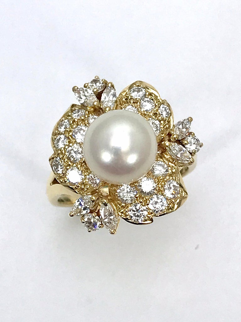 This is an elegantly ring.  Designed by Mikimoto, the 9.00 millimeter Cultured Pearl sits atop a floral Diamond cluster set in 18 karat yellow gold.  The Diamonds are made up of mainly round brilliant Diamonds, with six marquise shapes on the outer