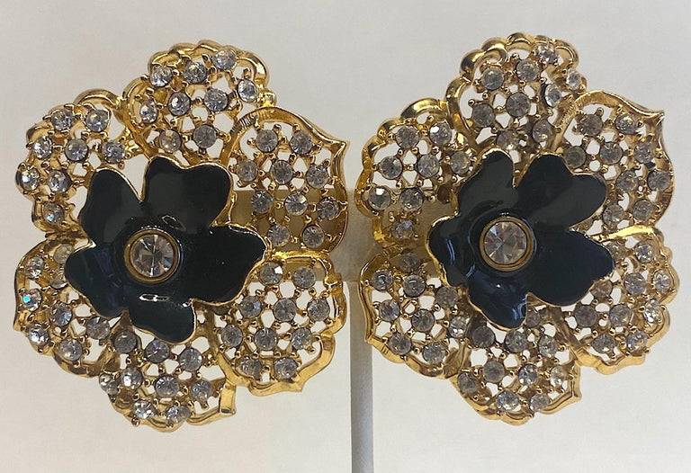 A truly stunning and like new condition pair of Mile Schön Milano flower earrings. The earrings have an open work design on the petals and set with round rhinestones. In the center is a smaller 1 inch diameter black enamel flower with large central