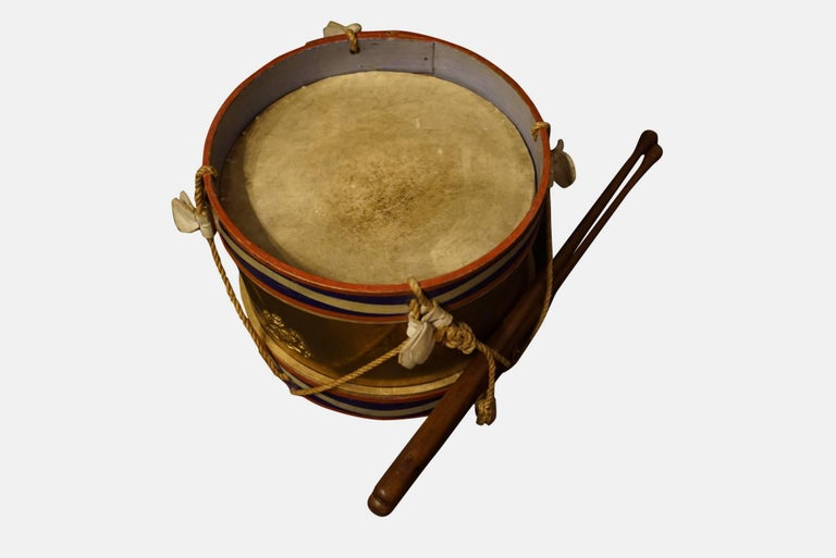 A military style drum for a child with pair of drumsticks,