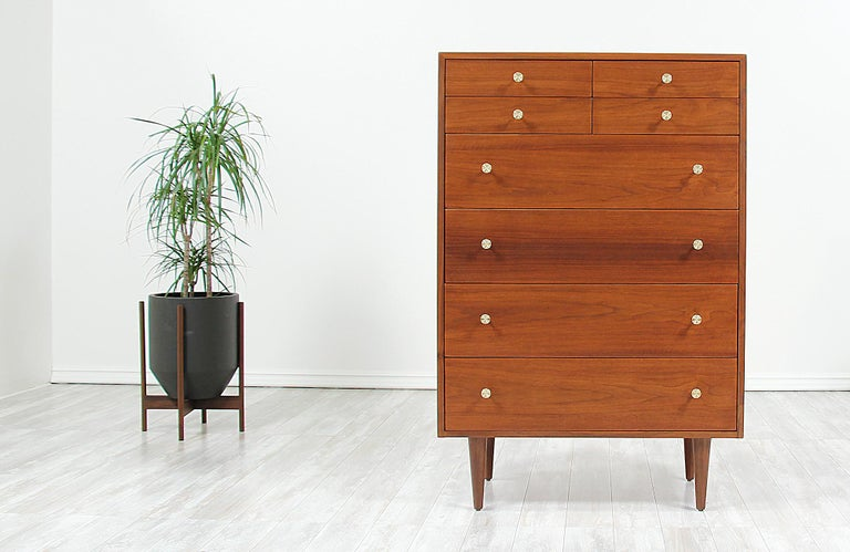 Spacious chest of drawers designed by Milo Baughman for Glenn of California in the United States, circa 1950s. This tall and elegant design features a sturdy construction in walnut wood with eight dovetailed drawers that vary in size. Two of the
