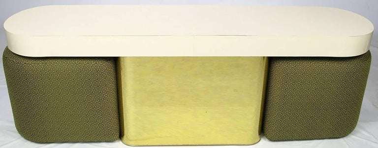 This console by Milo Baughman for Thayer Coggin features a brass-clad, radius-corner base, with a race track oval ivory micarta laminate top. The two newly upholstered benches or ottomans were designed to store under the tabletop. This would also