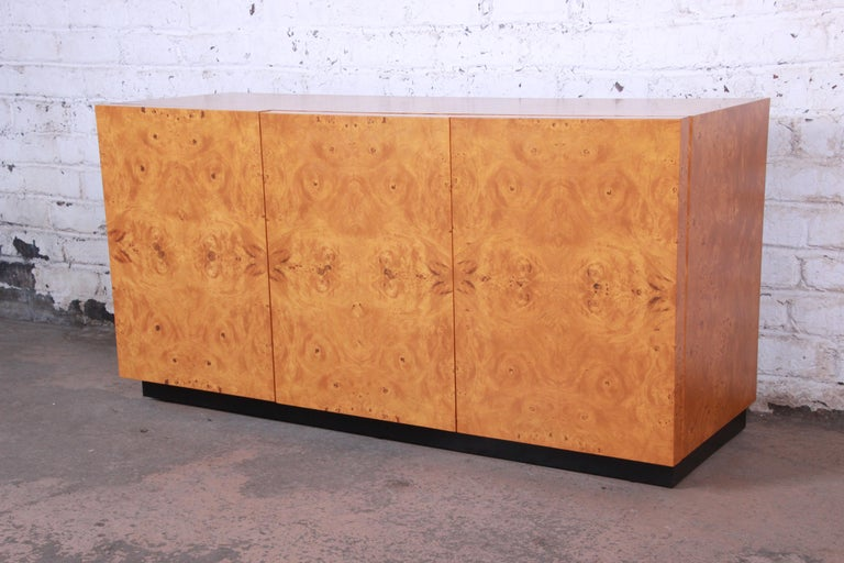 An exceptional Mid-Century Modern burled olive wood credenza or sideboard designed by Milo Baughman. The credenza features gorgeous burled wood grain, a nice black plinth base, and sleek midcentury design. It offers ample room for storage, with two