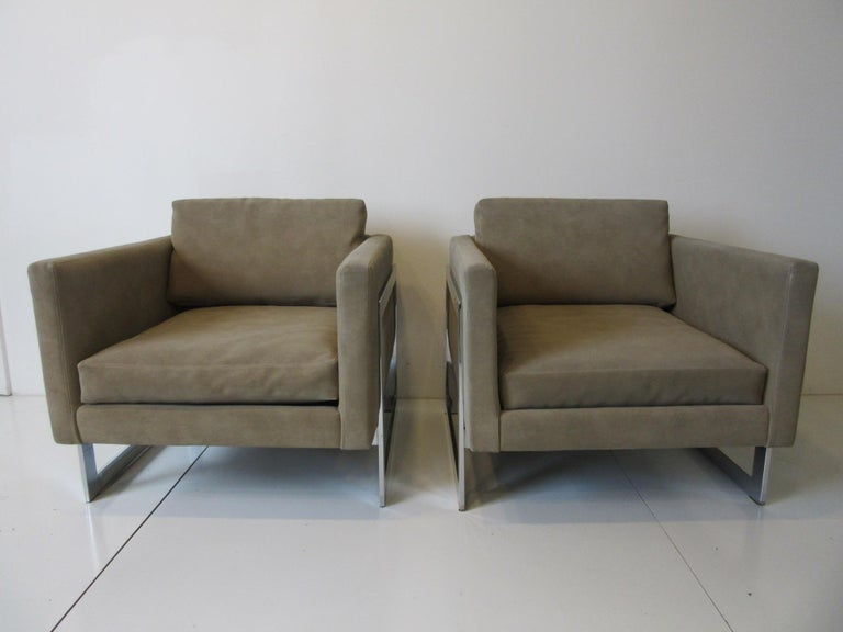A pair of cantilevered cube lounge chairs with loose back and bottom cushions in a dark sandy taupe ultra suede. Sitting on polished steel chromed frames and retaining the manufactures paper label by the Thayer Coggin furniture company, these fine