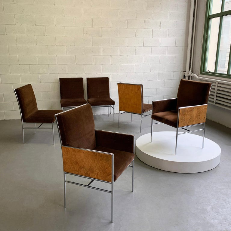 Set of six, Milo Baughman dining chairs feature tubular chrome frames with burl olive wood backs and sides with brown velvet upholstery. The set includes 4 side chairs at 22 inches wide and 2 captain armchairs.