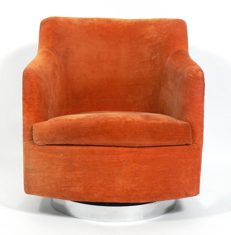 Curvaceous chrome swivel chair, designed by Milo Baughman, American, circa 1960s. Chrome has been hand polished. Retains original orange velvet style fabric. We can reupholster it for you in your fabric for an additional $400 if you prefer.