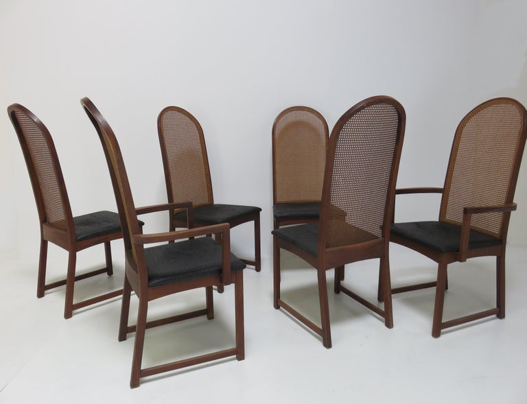 A set of six dining chairs by Milo Baughman. Comprising four side chairs and two armchairs, each with cane backs and black vinyl seats with mahogany frames.