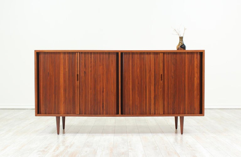Mid Century Modern Credenza designed by Milo Baughman for Glenn of California in the United States c. 1950s. Crafted in walnut wood, this exceptional credenza features two compartments, each with its set of tambour doors and carved, recessed