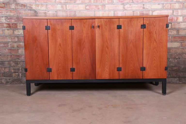 A gorgeous Mid-Century Modern sideboard credenza or bar cabinet  By Milo Baughman for Directional  USA, 1960s  Bookmatched walnut, with ebonized base and accents.  Measures: 54.5