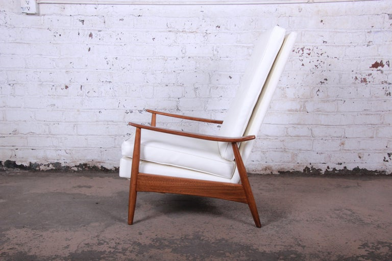 An exceptional Mid-Century Modern reclining lounge chair designed by Milo Baughman for James Inc. The chair features a gorgeous sculptural walnut frame and original white vinyl upholstery in excellent condition. The frame has been professionally