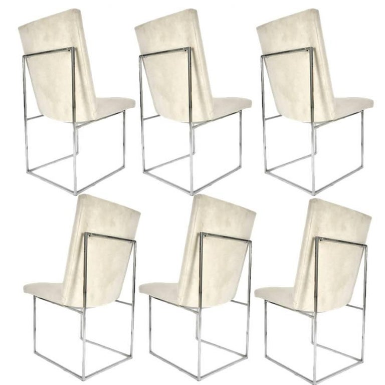 One of Milo Baughman's more iconic designs. These dining chairs have a stunning architectural base of polished chrome square stock metal supporting a floating seat and back. Upholstered in off-white original ultra-suede.