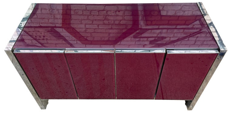 This is a beautiful Milo Baughman for Thayer Coggin sideboard or credenza in purple glass top and glass front doors chrome base and trim. This glass sideboard features 4 cabinets. In wonderful condition labeled inside. Two front left doors have