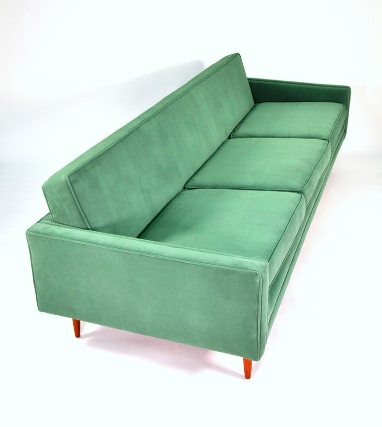 A Mid-Century Modern couch with walnut legs, dating from the 1950s and newly reupholstered in a light emerald green cotton velvet. The vintage three-seat sofa, designed by Milo Baughman for Thayer Coggin, features loose cushions and round tapered