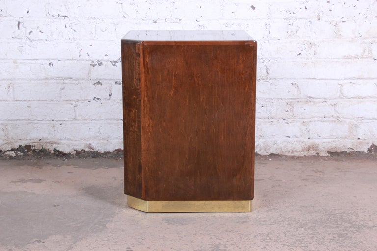 A gorgeous Mid-Century Modern cube side table or pedestal table designed by Milo Baughman for Thayer Coggin. The table features stunning bird's-eye maple grain and a sleek brass plinth base. It has a unique design, with a single canted corner. The