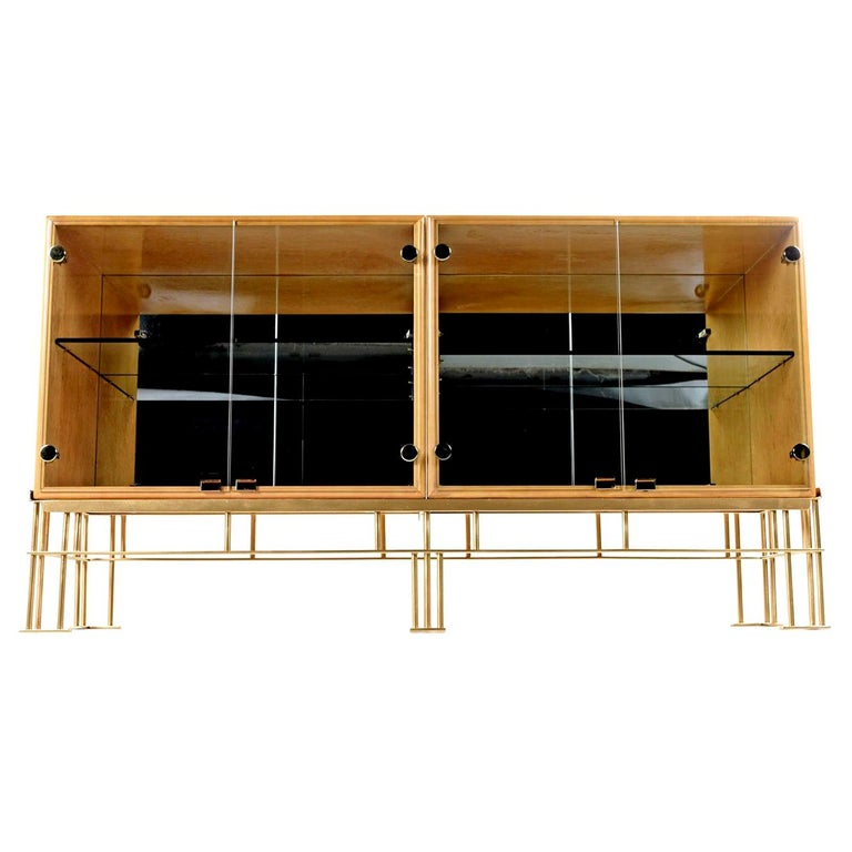 These iridescent lacquered solid bird's-eye maple wood cabinets with their polished brass accents are sure to make this piece the focal point of any room. The two glass door cabinets features a mirrored back and adjustable glass shelf, allowing it