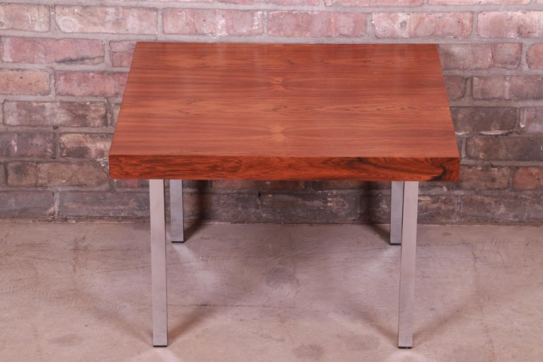 An exceptional Mid-Century Modern occasional side table  By Milo Baughman for Thayer Coggin  USA, 1966  Bookmatched rosewood top, with polished chrome legs.  Measures: 24