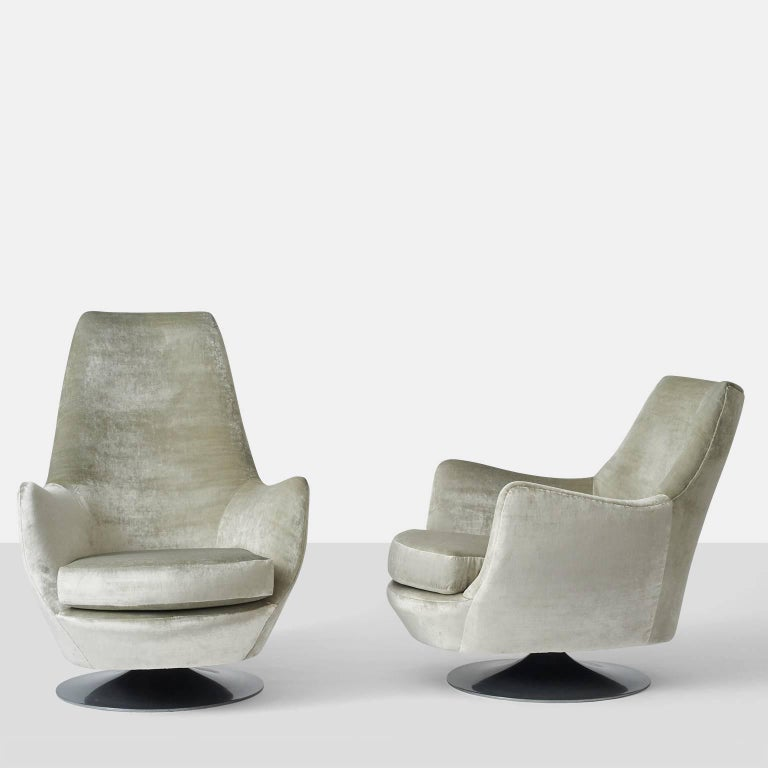 A pair of Milo Baughman his and hers swivel lounge chairs upholstered in a silver/gray toned velvet on a aluminum base.