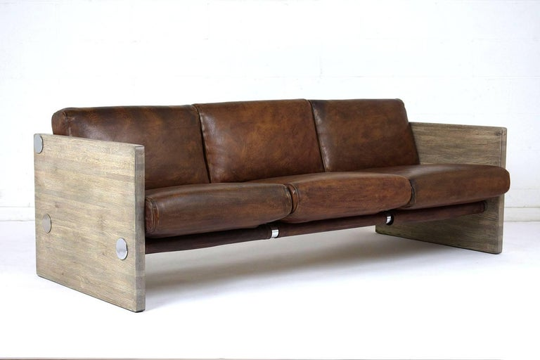 This 1960s Mid-Century Modern three-seat sofa features a sleek profile with wood armrests and steel bar supports. The wood arms have a stacked wood look with a faded finish. The comfortable cushions are upholstered in leather with single piping trim