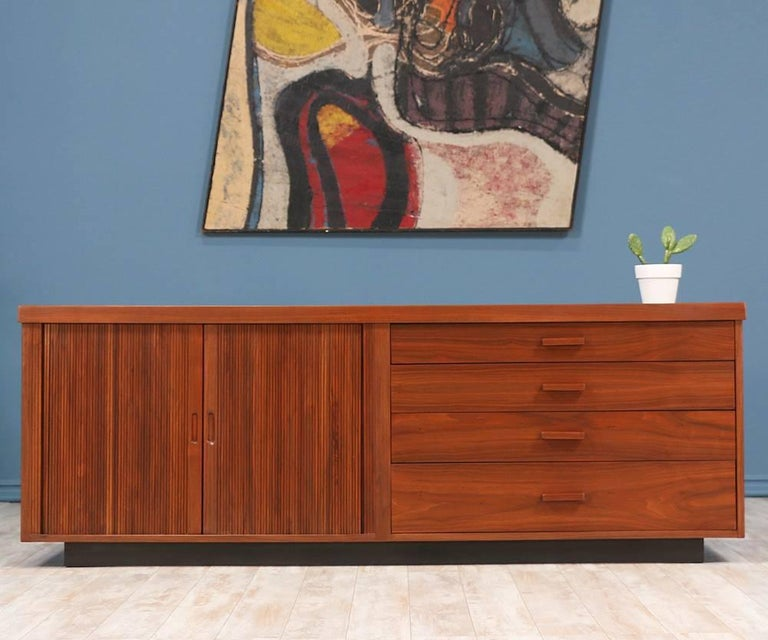 Mid Century Modern Credenza designed by Milo Baughman for Glenn of California in the United States c. 1950's. This beautiful storage piece is comprised of walnut wood. The left side features two tambour doors with recessed pulls that reveal a