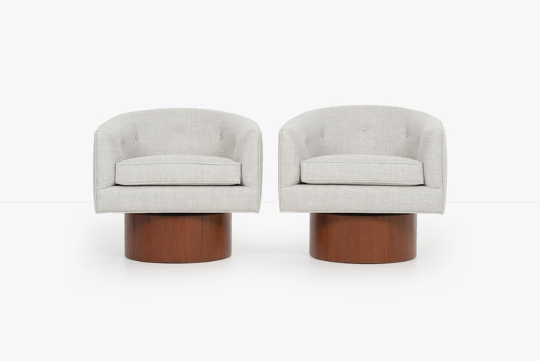 Milo Baughman pair of lounge chairs, oiled walnut swivel bases reupholstered with great plains cotton blended fabric.