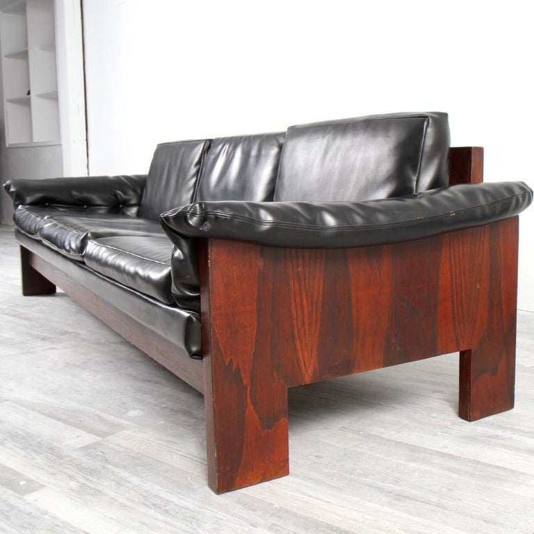 Relatively rare example of Baughman's Brazillian-influenced design for Thayer Coggin. Thick, leather-like naugahyde with dark rosewood frame. Part of a set (others sold separately) which include a chair and ottoman and loveseat.