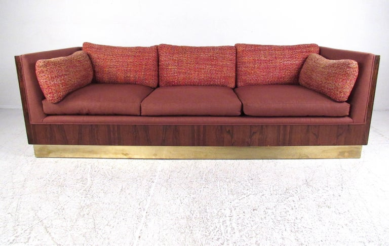 This stunning midcentury sofa by Milo Baughman features stylish vintage fabric, rich rosewood frame, and brass finish baseboard. Plush upholstered cushions feature unique two-tone covering, and makes an impressive statement in home or business