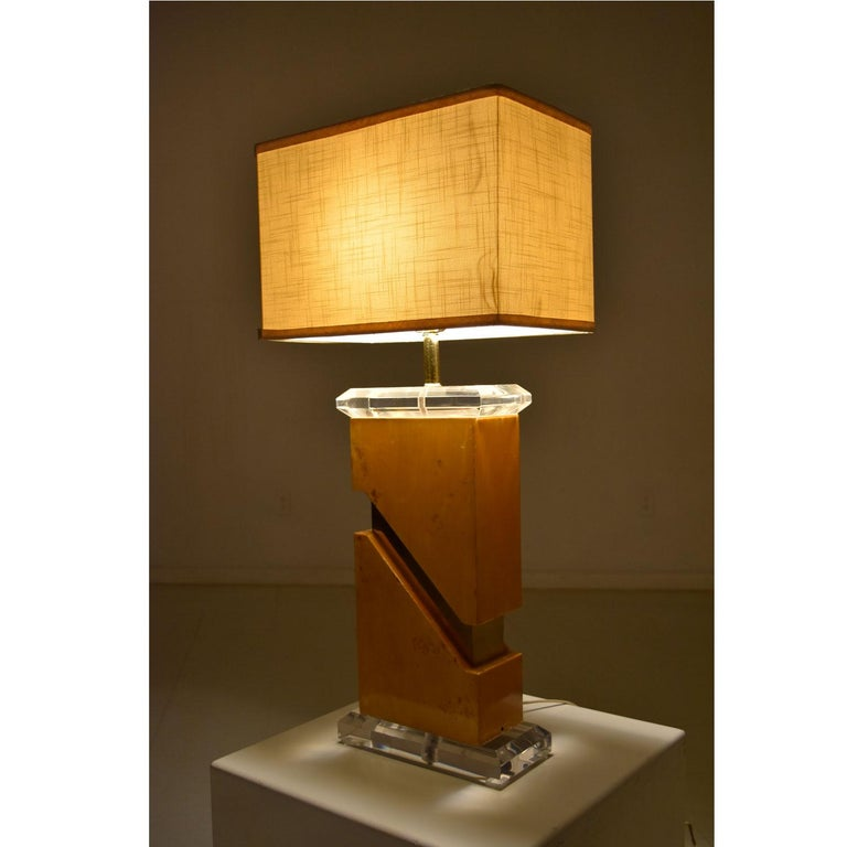 We're not certain who made this amazing lamp, but it looks similar to the works of Leon Rosen, Milo Baughman and Pierre Cardin. Hollywood Regency and Mid-Century Modern design intertwine like the elements it's formed from. Burl, Lucite and brass