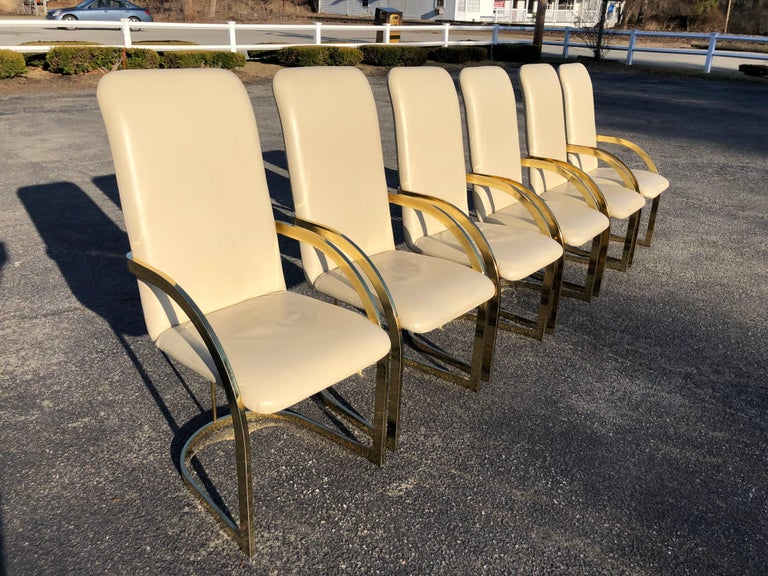 Milo Baughman style brass and leather set of chairs. Gorgeous from any angle these chairs are extremely comfortable and support with their high backs. Seat width is 18.75, seat depth is 18.50. The top of the arm rests are 26.75.