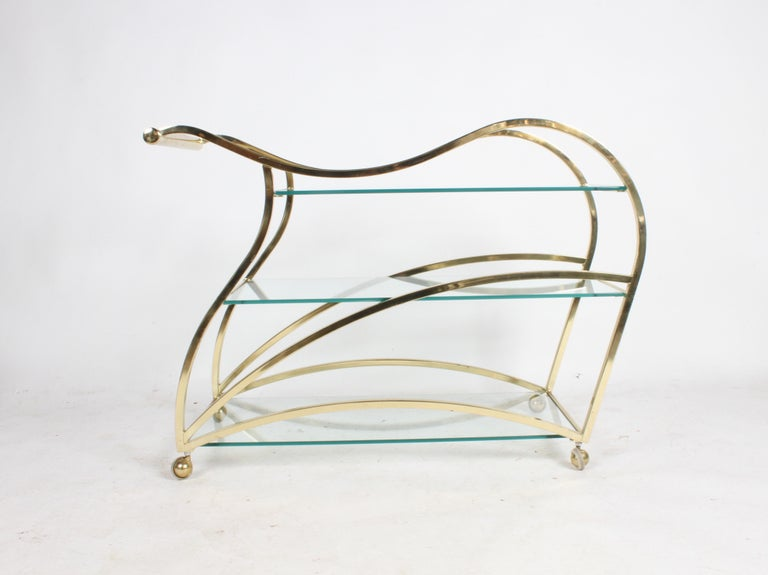 Design Institute of America designed brass sculptural bar cart, a true piece of art. This rarely seen cart is in very nice original condition. Minor wear to brass on handles, few light scratches to glass, light patina. Often attributed to Milo