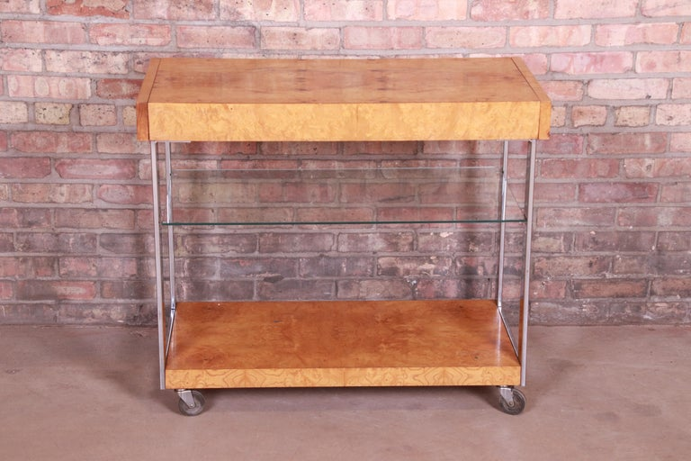 An exceptionalMid-Century Modern extension bar cart  In the manner of Milo Baughman  By Lane Furniture  USA, 1970s  Book-matched burled olive wood, with chrome legs, a single glass shelf, and original casters.  Measures: 36.13