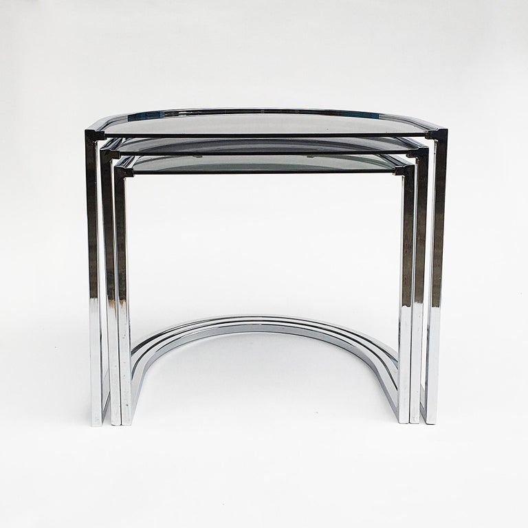 A minimal smoked glass top and chrome nest tables in the style of Milo Baughman. Curved elegant yet modern lines. Two pairs of nest table available, listing is for one.