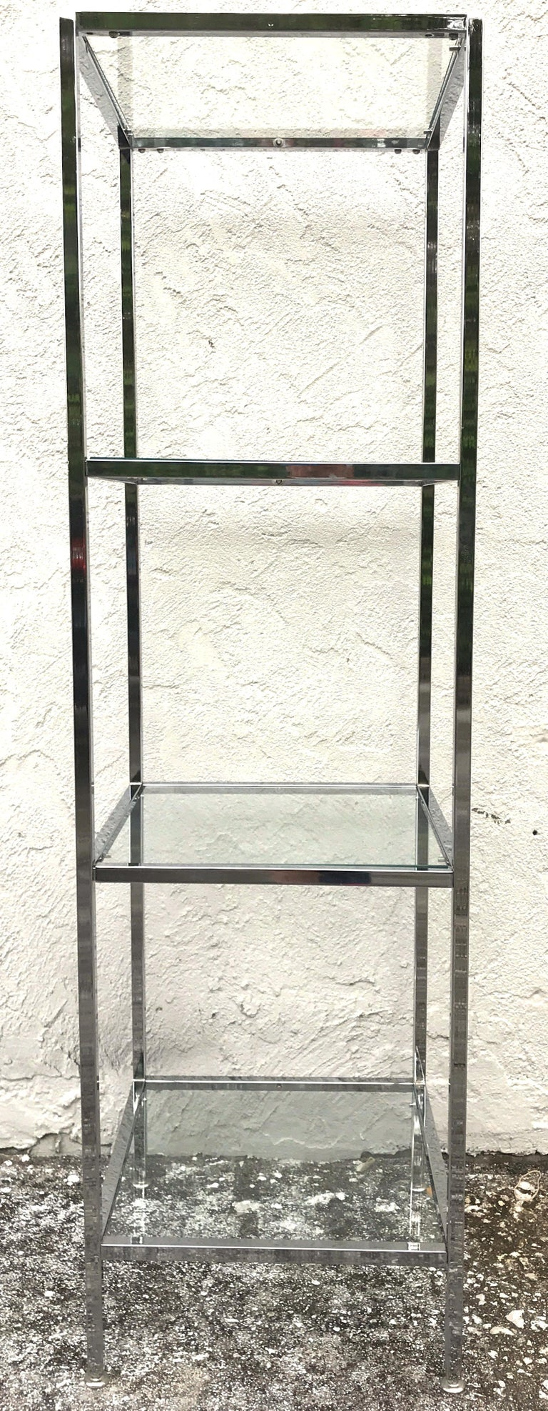 Milo Baughman style tall chrome and glass column étagère,  Each one fitted with four 17 inch square clear glass shelves. Each cube shelf has a display height of 17.5