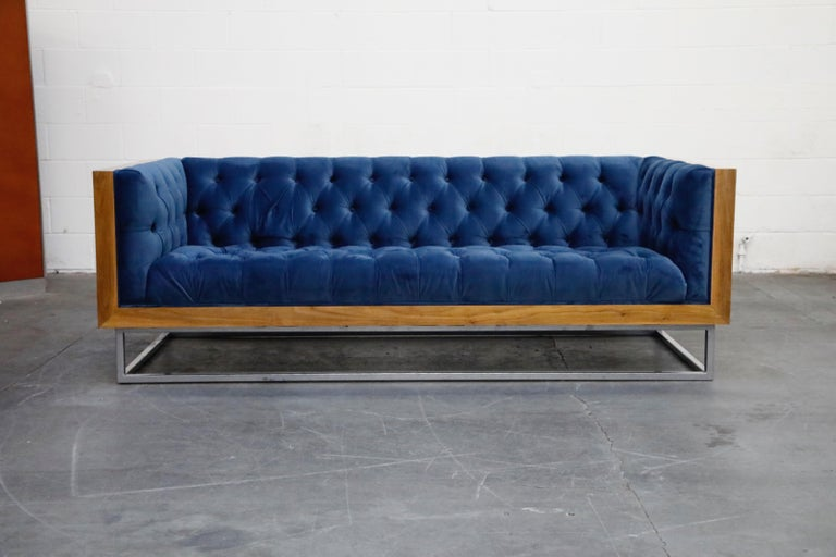 This high quality, well made custom case sofa in the style of Milo Baughman for Thayer Coggin features a hefty wood case design floating on top of a thick steel base. The vibrant blue velvet tufted upholstery features one row of buttons in