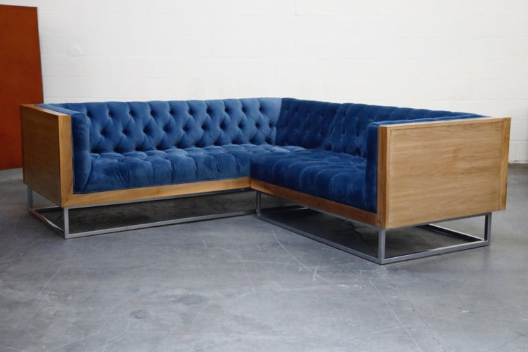 This high quality, well made, custom sectional sofa in the style of Milo Baughman for Thayer Coggin features a hefty wood case design floating on top of a thick steel base. The vibrant blue velvet tufted upholstery features one row of buttons in