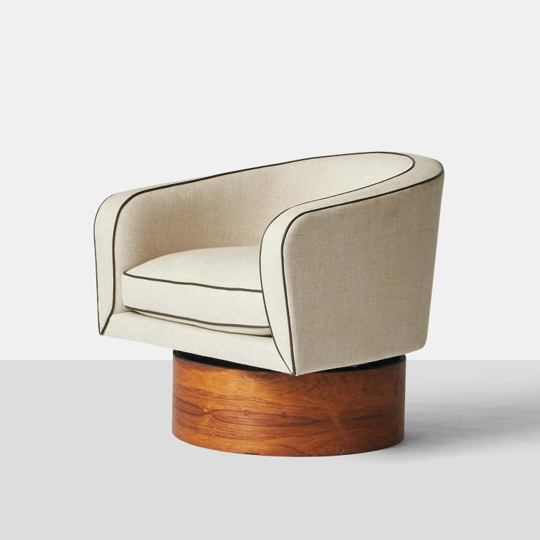 A tall, Barrel shaped club chair by Milo Baughman for Thayer Coggin. Features a high, cushioned seat, and round walnut base. Shown in beige linen, with contrasting brown piping.