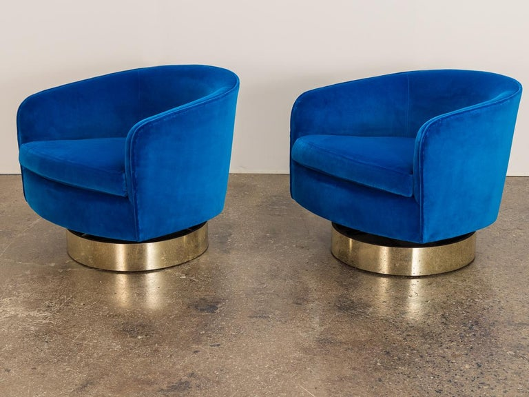 Pair of glamorous 1970s velvet swivel lounge chairs, designed by Milo Baughman for Thayer Coggin. These plush chairs have a tilt feature for added function and comfort. Gleaming gilt bases have been restored with new brass plating. Newly recovered