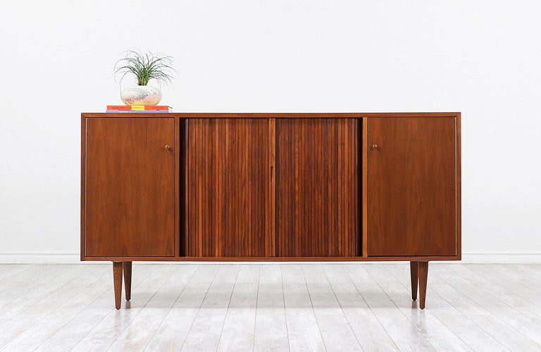 Mid-Century Modern credenza designed by Milo Baughman for Glenn of California in the United States circa 1950s. This exceptional credenza is crafted in walnut wood that features a closed shelved compartment on each side and a set of tambour doors