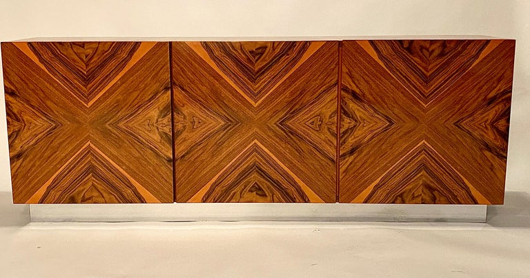 Rosewood wall mounted cabinet designed by Milo Baughman for Thayer Coggin. This rare floating wall cabinet is made in a gorgeous rosewood parquetry with a French polish finish and a chrome plinth.   The three cabinet doors open to reveal two