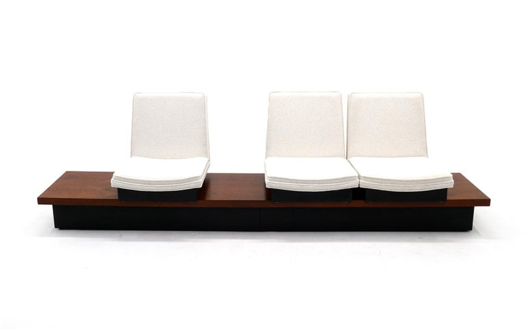 Something we have never seen. Designed by Milo Baughman and made by Thayer Coggin, this is a three seat seating unit that consists of a nine foot long bench style platform of walnut with a black lacquered plinth base. The three seats which have been