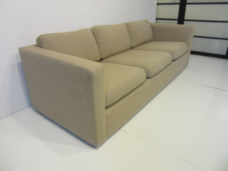 A tuxedo styled three cushion sofa in a tightly woven contract fabric in a sandy beige tone having a simple design with comfort. Retains the manufactures label by the Thayer Coggin Furniture company.